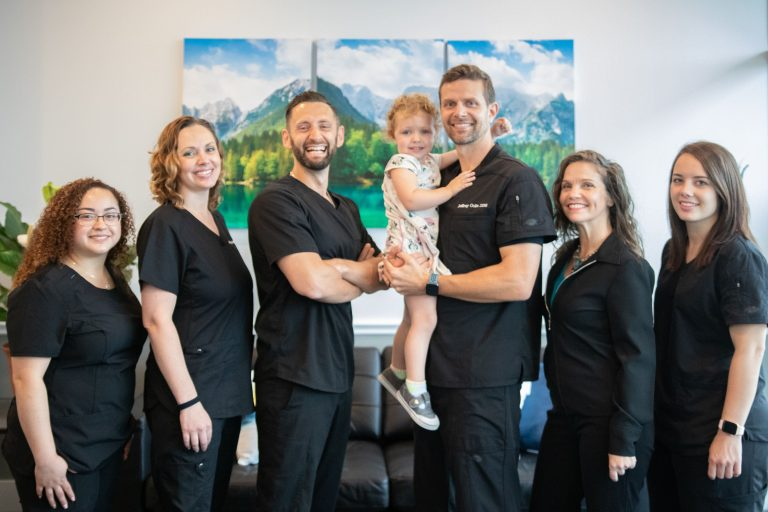 JA Advanced Family Dental - Team posing alongside a child